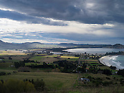 High-angle view of Karitane, Otago, New Zealand, with Cornish Head in the background.  Sunlight breaks through the clouds to highlight Karitane.