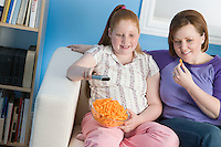 Overweight girl and mother watching television on sofa