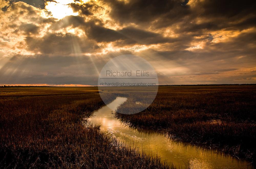 Sun breaks through a cloudy sky on the marsh near the Isle of Palms, SC.