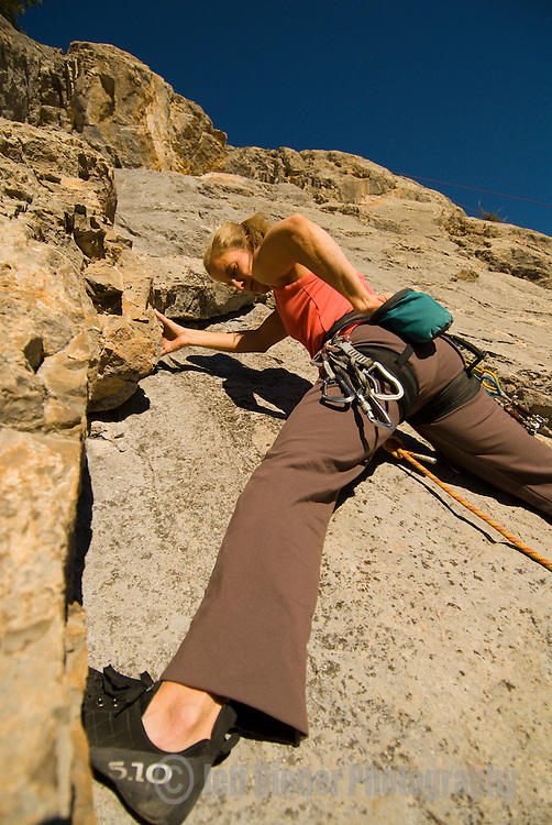A young woman rock climbs at the Hoback Shield in Jackson Hole, Wyoming.