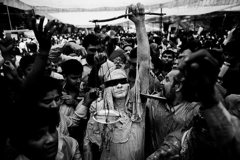 A supporter of social activist Anna Hazare dresses up like the blind lady of justice as others rejoice the ocassion after the government agreed to all the terns set by Anna Hazare, in New Delhi, India, on Saturay April 9, 2011. Hazare has vowed to fast to the death to rid India of the corruption he says is its biggest curse. Photographer: Prashanth Vishwanathan