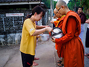13 JANUARY 2019 - NAKHON PATHOM, THAILAND: A woman gives food to female monks from Wat Songdhammakalyani on their alms rounds. The Sangha Supreme Council, Thailand's governing body of Buddhist monks, bans the ordination of female monks, but hundreds of Thai women have gone abroad, mostly to Sri Lanka and India, to be ordained. There are about 270 women monks in Thailand and about 250,000 male monks. There are 7 monks and 6 novices at Wat Songdhammakalyani in Nakhon Pathom. It was the first temple in Thailand to have female monks. The temple opened 60 years ago and has always been a temple of women monks. Women can be ordained as novices in Thailand, but to be ordained as a full monk would require the participation of 10 female monks and 10 male monks, and male monks in Thailand are barred from participating in women's ordination ceremonies.    PHOTO BY JACK KURTZ