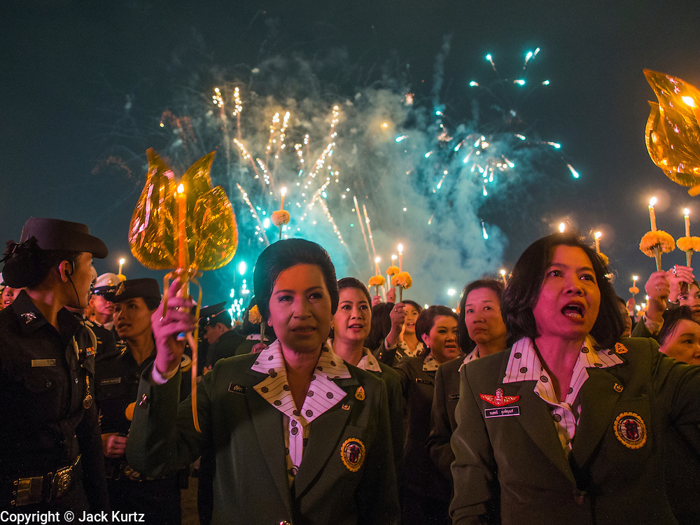 05 DECEMBER 2013 - BANGKOK, THAILAND: Fireworks go off while Thais hold candles to honor the King. Thais observed the 86th birthday of Bhumibol Adulyadej, the King of Thailand, their revered King on Thursday. They held candlelight services throughout the country. The political protests that have gripped Bangkok were on hold for the day, although protestors did hold their own observances of the holiday. Thousands of people attended the government celebration of the day on Sanam Luang, the large public space next to the Grand Palace in Bangkok.     PHOTO BY JACK KURTZ