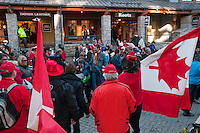 Fans carrying Swiss and Canadian flags meet for a friendly talk in the village stroll during the 2010 Olympic Winter Games in Whistler, BC Canada