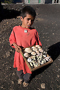 Native boy selling something in front of his house, vulcano in background. Fogo. Cabo Verde. Africa.