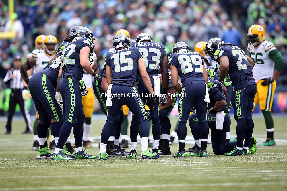 the Seattle Seahawks offense huddles as the Green Bay Packers defense looks on during the NFL week 20 NFC Championship football game against the Green Bay Packers on Sunday, Jan. 18, 2015 in Seattle. The Seahawks won the game 28-22 in overtime. ©Paul Anthony Spinelli
