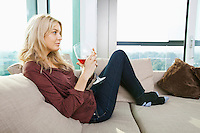 Side view of young woman with wine glass in living room at home