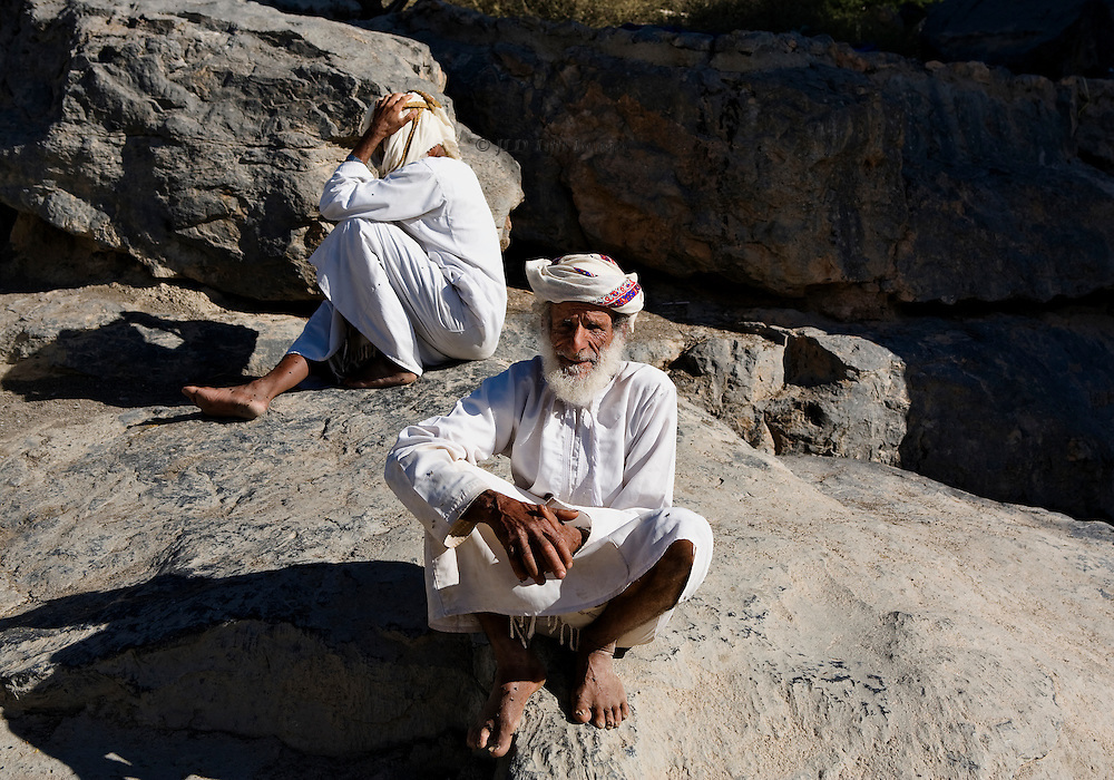 Two men seated on a vast boulder in the Omani village of Misfah.  They wear traditional Omani dress of dishdasha and turban. One turns his head away and covers his face with one hand, not wanting his visage captured in the camera.