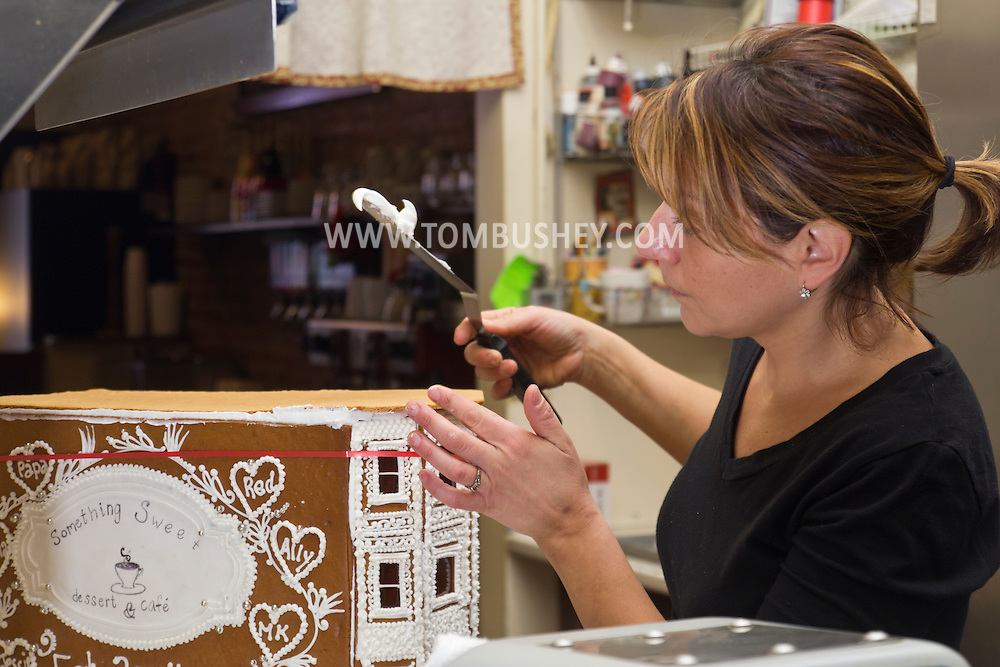 Middletown, New York - A baker adds icing to a gingerbread house at Something Sweet Dessert Cafe on Nov. 23, 2014.