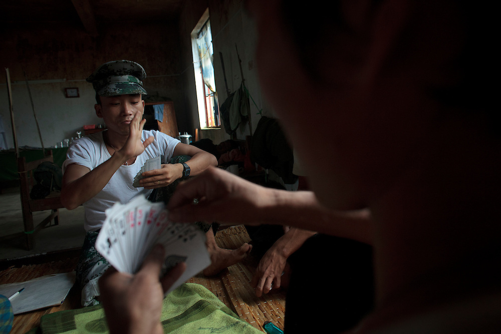 Kachin's militia member Lalaw Ze Dai, from Waimaw village, 25, play cards with his hospital mates in the General Military Hospital in Laiza village close to the China border, Myanmar on July 28, 2012.  He was injured by a landmine in June, 26, 2012 loosing part of his right leg on top of knee.