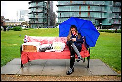 A lady sits in the rain with her hamper wrapped up as Royal Fans wait to watch the Royal Pageant at Tower Bridge during the Queen's Diamond Jubilee weekend, Sunday June 3, 2012. Photo By Andrew Parsons/i-Images