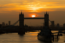 © Licensed to London News Pictures. 17/10/2017. LONDON, UK.  Sunrise behind Tower Bridge on the River Thames in London this morning, behind a hazy and colourful sky.  Photo credit: Vickie Flores/LNP