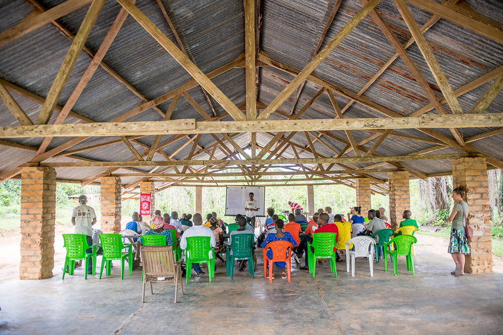 A group gathers for a presentation under a pavilion in Ganta, Liberia