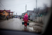 A woman with buckets on the way to get drinking water in Marginenii de Jos where are still houses which are not connected to a water pipe system.