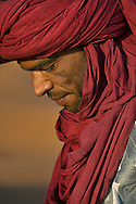 Portrait of a Moroccan man with red turban in the Moroccan Sahara desert.