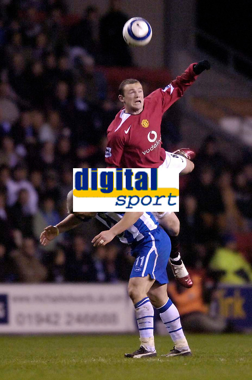 Photo: Jed Wee.<br /> Wigan Athletic v Manchester United. The Barclays Premiership. 06/03/2006.<br /> <br /> Manchester United's Wayne Rooney (R) goes flying over the back of Wigan's Graham Kavanagh.