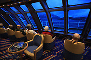 Passengers view mountains near Trollfjorden from observation deck of Hurtigruten ship on a stormy night in early May sailing northward from Lofoten Islands along west coast of Norway.