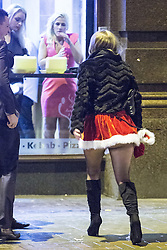 """© Licensed to London News Pictures . 20/12/2014 . Manchester , UK . A woman in a santa costume crosses Deansgate . """" Mad Friday """" revellers out in the rain and cold in Manchester . Mad Friday is typically the busiest day of the year for emergency services , taking place on the last Friday before Christmas when office Christmas parties and Christmas revellers enjoy a night out .  Photo credit : Joel Goodman/LNP"""