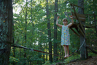 Jessica Laman (age 9) practices her slack lining (tight rope walking) in the back woods.<br />