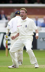 Warwickshire's Allan Donald celebrates after taking the wicket of Tim Hancock, seen walking back to the pavilion, during the NatWest Trophy cricket Final at Lords' in London.