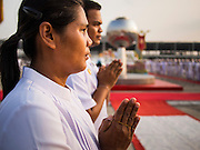 "14 FEBRUARY 2014 - KHLONG LUANG, PATHUM THANI, THAILAND: A woman prays during the opening of evening Makha Bucha Day services at Wat Phra Dhammakaya. The aims of Makha Bucha Day are: not to commit any kind of sins, do only good and purify one's mind. It is a public holiday in Cambodia, Laos, Myanmar and Thailand. Many people go to the temple to perform merit-making activities on Makha Bucha Day. The day marks four important events in Buddhism, which happened nine months after the Enlightenment of the Buddha in northern India; 1,250 disciples came to see the Buddha that evening without being summoned, all of them were Arhantas, Enlightened Ones, and all were ordained by the Buddha himself. The Buddha gave those Arhantas the principles of Buddhism, called ""The ovadhapatimokha"". Those principles are:  1) To cease from all evil, 2) To do what is good, 3) To cleanse one's mind. The Buddha delivered an important sermon on that day which laid down the principles of the Buddhist teachings. In Thailand, this teaching has been dubbed the ""Heart of Buddhism."" Wat Phra Dhammakaya is the center of the Dhammakaya Movement, a Buddhist sect founded in the 1970s and led by Phra Dhammachayo.    PHOTO BY JACK KURTZ"