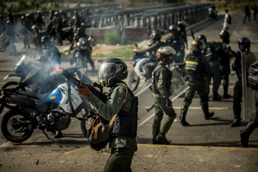 CARACAS, VENEZUELA - MAY 24, 2017: National Guard soldiers fire tear gas canisters at anti-government protesters. The streets of Caracas and other cities across Venezuela have been filled with tens of thousands of demonstrators for nearly 100 days of massive protests, held since April 1st. Protesters are enraged at the government for becoming an increasingly repressive, authoritarian regime that has delayed elections, used armed government loyalist to threaten dissidents, called for the Constitution to be re-written to favor them, jailed and tortured protesters and members of the political opposition, and whose corruption and failed economic policy has caused the current economic crisis that has led to widespread food and medicine shortages across the country.  Independent local media report nearly 100 people have been killed during protests and protest-related riots and looting.  The government currently only officially reports 75 deaths.  Over 2,000 people have been injured, and over 3,000 protesters have been detained by authorities.  PHOTO: Meridith Kohut