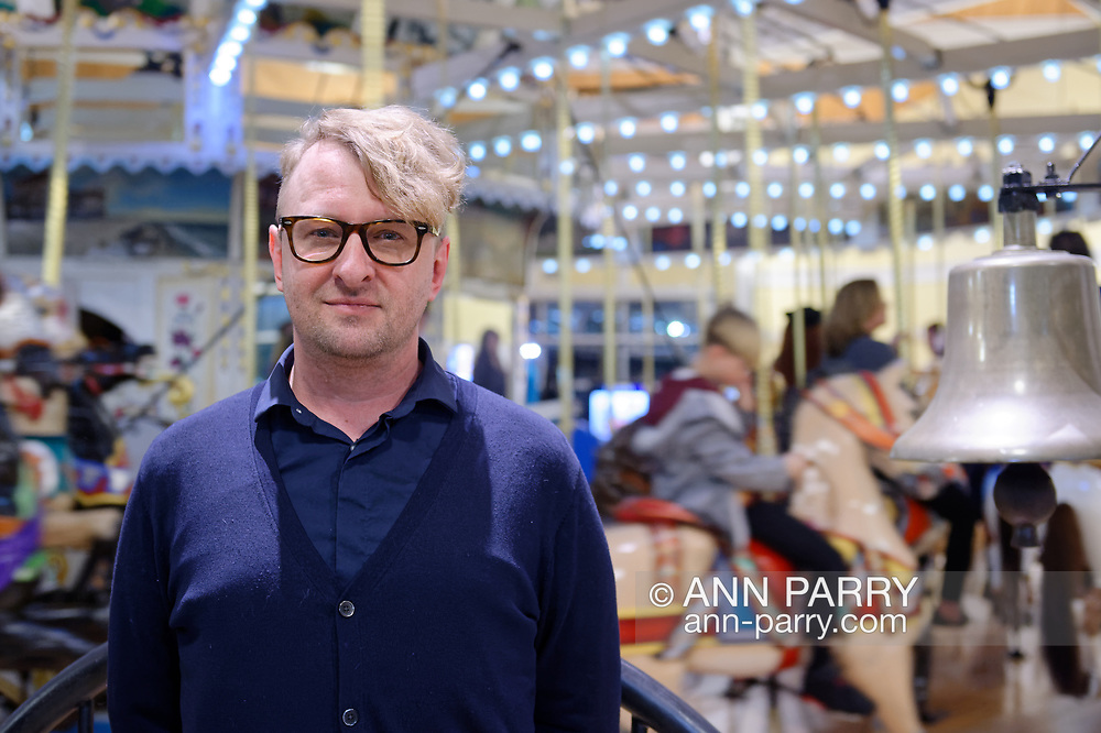 Garden City, New York, USA. March 9, 2019. Artist MICHAEL WHITE stands in front of Nunley's Carousel during Unveiling Ceremony of his mural of the carousel's lead horse.