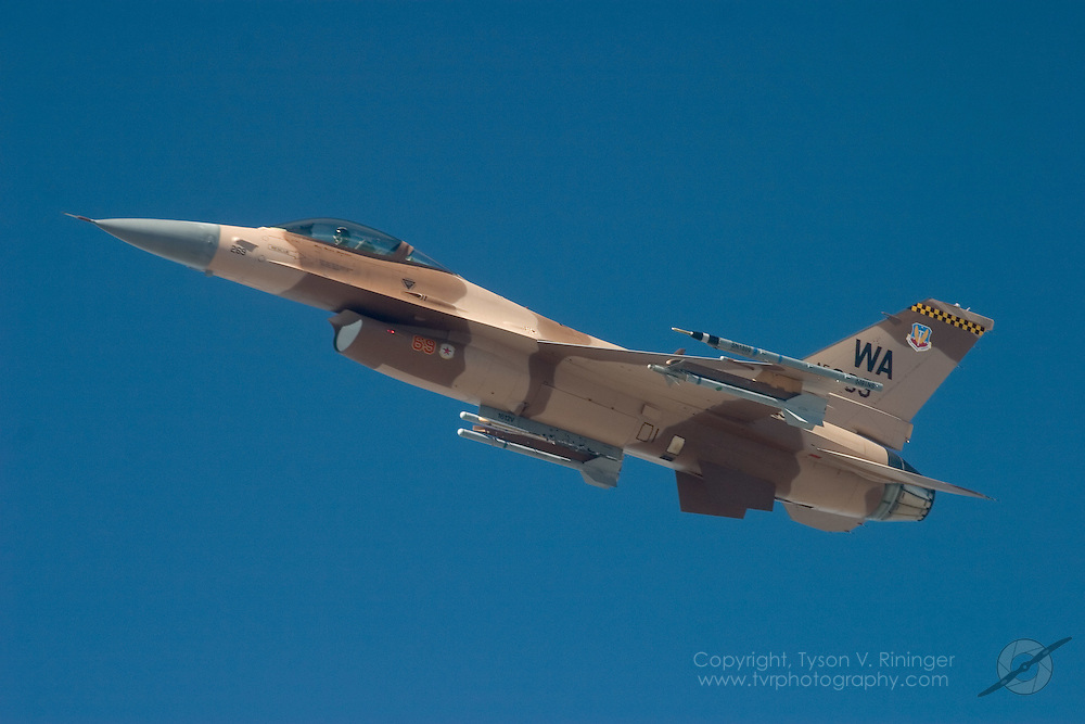 One of the many different camoflouges used by the 64th Aggressor Squadron is illustrated by the F-16C wearing desert camo. Other variations include a blue-grey scheme and a green-brown scheme.