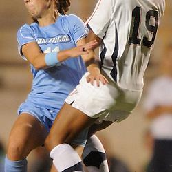 San Diego junior midfielder Sierra Ferreira (11) collides with Cal State Fullerton freshman midfielder Chelsey Patterson (19) during Fullerton's 2-0 victory on Sept. 22, 2011 at Titan Stadium.
