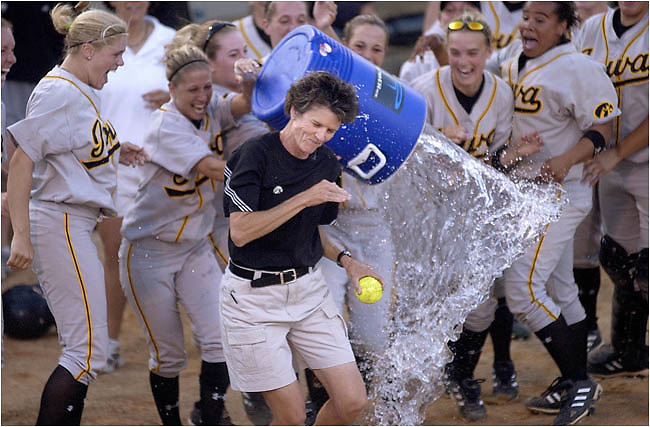 Iowa head coach Gayle Blevins tries to escape a dousing of water by her players after she won the 1,000th game of her career and her 700th coaching for Iowa. Iowa defeated Coe college 9-1 in six innings Friday, April 16, 2004 at Pearl Field in Iowa City.