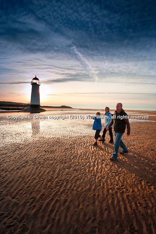 Family (parents and young son walking at sunset<br /> Wales Coast Path<br /> Talacre Lighthouse<br /> Near Point of Ayr<br /> Flintshire<br /> North<br /> Activities and Sports