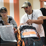 OCTOBER 6, 2017--MAYAGUEZ, PUERTO RICO ---<br /> Dolores Morales, Executive Director of Migrant Health Center  listens to Daniel Ramos of the Asociacion de Salud Primaria de Puerto Rico as she receives medical supplies from Direct Relief following the path of Hurricane Maria through Puerto Rico.<br /> (Photo by Angel Valentin/Freelance)