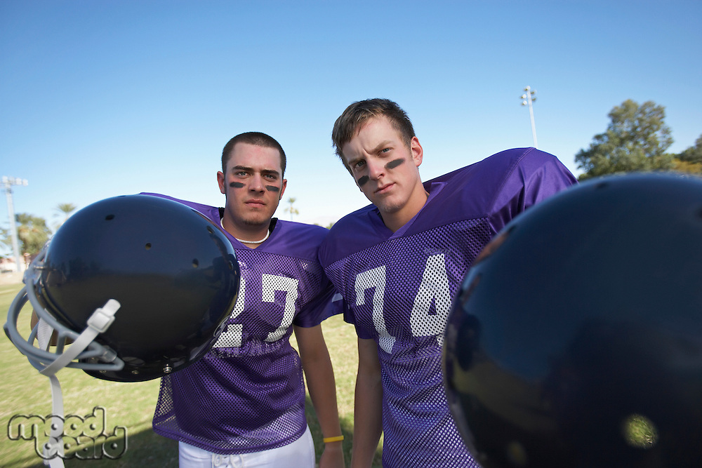 Two Football Players Holding Helmets