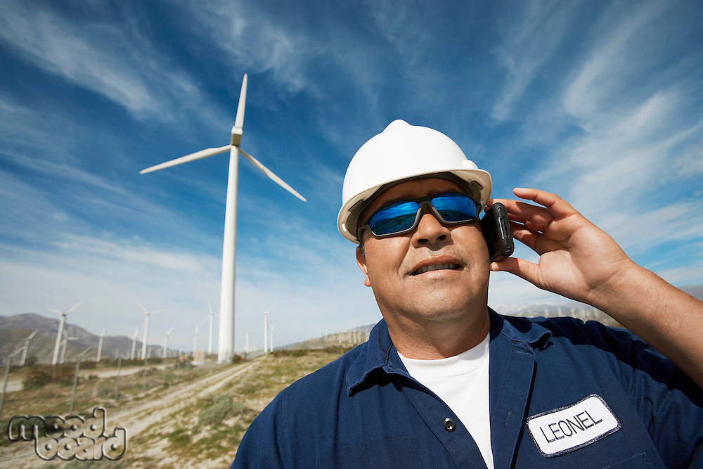 Engineer using mobile phone at wind farm, portrait