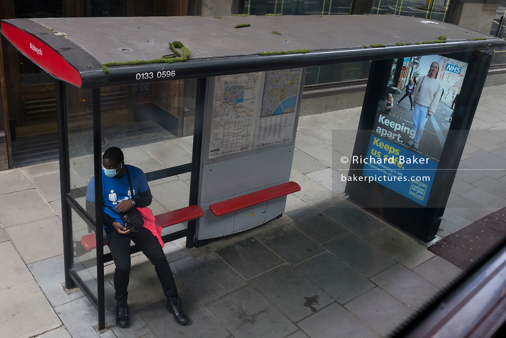 With a further 89 UK covid victims in the last 24hrs, bringing the total victims to 43,995 during the Coronavirus pandemic, a man wearing social distance t-shirt (worn by railway station concourse employees), sits at a bus stop next to an ad urging Londoners to stay apart, on 2nd July 2020, in London, England.
