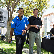 """UCLA football quarterback Brett Hundley and coach Jim Mora compete in a game of bean bag toss. Hundley's team won the challenge despite a few """"inadvertent"""" bumps from Coach Mora."""