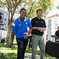 "UCLA football quarterback Brett Hundley and coach Jim Mora compete in a game of bean bag toss. Hundley's team won the challenge despite a few ""inadvertent"" bumps from Coach Mora."