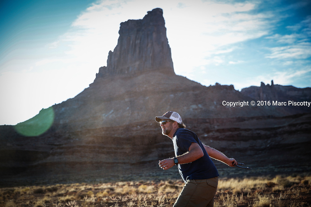SHOT 10/16/16 5:51:21 PM - Doug Starkey of Steamboat, Co. tossing horseshoes after riding all day on the White Rim trip. The White Rim is a mountain biking trip in Canyonlands National Park just outside of Moab, Utah. The White Rim Road is a 71.2-mile-long unpaved four-wheel drive road that traverses the top of the White Rim Sandstone formation below the Island in the Sky mesa of Canyonlands National Park in southern Utah in the United States. The road was constructed in the 1950s by the Atomic Energy Commission to provide access for individual prospectors intent on mining uranium deposits for use in nuclear weapons production during the Cold War. Four-wheel drive vehicles and mountain bikes are the most common modes of transport though horseback riding and hiking are also permitted.<br /> (Photo by Marc Piscotty / &copy; 2016)