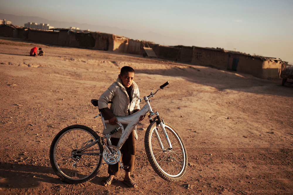 Pakistan/ Afghan refugees/ A boy holds his bike in I-11 refugee camp in Islamabad. Afghan refugees were resettled here from another location in Islamabad two years ago. Residents compain that they have inadequate water pumps and supply of electricity. The majority of men work as labourers in the Rawalpindi vegetable market, less than one kilometre from the camp. They earn on average 300-400 ($4-$5) a day. Afghan nomad sheperds also settle in the area over the winter months with their flocks of sheep. Many of the refugees here lived in a Haripur refugee camp on their arrival to Pakistan 30 years ago after the occupation of Afghanistan in 1979 by Soviet forces. They then resettled in Islamabad over the last 18 years. UNHCR/Sam Phelps/ November 2011