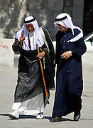 old arab men walking and talking in street