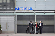 Asian businessmen in front of Nokia Building.