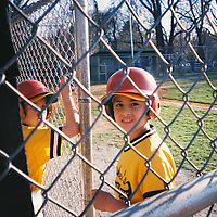 1. When was this photo taken? <br /> <br /> Don't know - found the roll<br /> <br /> 2. Where was this photo taken? <br /> <br /> Some little league baseball field.<br /> <br /> 3. Who took this photo?<br /> <br /> Don't know - found the roll<br /> <br /> 4. What are we looking at here?<br /> <br /> Little league baseball player looking at camera through the fence. his face is framed by the opening in the fence. his team mate is there, but his face is obscured by the fence.<br /> <br /> 5. How does this old photo make you feel? <br /> <br /> The expression on the face of the player is mixed. the mouth seems to be smiling but the eyes are questioning. the expression is is part 'mom (or dad, or whoever), why are you taking my picture, here, in front of my friends?' and part 'a young man growing up, showing confidence'.<br /> <br /> 6. Is this what you expected to see?<br /> <br /> I found this roll and have kept it around for 15 years or more. your project got me to send it to you to be developed to see what was on there. kind of a surprise to see what was there - just pictures of some house (outside and inside empty - maybe they are moving in or moving out?) and the two baseball pictures.<br /> <br /> 7. Does this photo bring back any memories?<br /> <br /> Yes - little league!<br /> <br /> 8. How do you think others will respond to this photo?<br /> <br /> I hope they also see the duality in the facial expression.