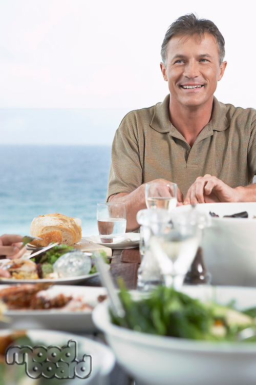Smiling Man Eating meal outside near the sea