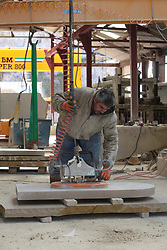 Covid 19 - Stonemason Justin Warren prepares a headstone, one of an increasing daily number (9 that day) being ordered from the Purbeck stone quarry at St Aldhelm's, Dorset. UK April 2020