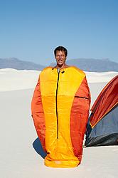 man having fun while standing in a zipped sleeping bag in the desert