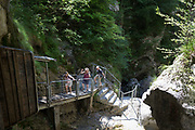 Visitors climb steps between the rocky gorge at the WW2-era Franja Partisan Hospital, on 20th June 2018, near Dolenji Novaki, Slovenia. From December 1943 until the end of the war as part of a broadly organized resistance movement against the Fascist and Nazi occupying forces, the hospital was set in a deep gorge in rural Slovenia where fighters were brought in from many areas to be treated in this secret location. 578 were treated here but the mortality rate were only 10% and the site was never discovered by German forces. Franja is in the UNESCO Tentative List of World Heritage sites.