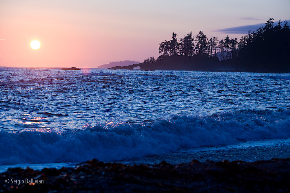 West Coast Trail - Day 3.  The sun sets behind the hole-in-the-wall point as waves break on the beach.