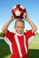 Girl (7-9 years) soccer player holding ball above head, portrait