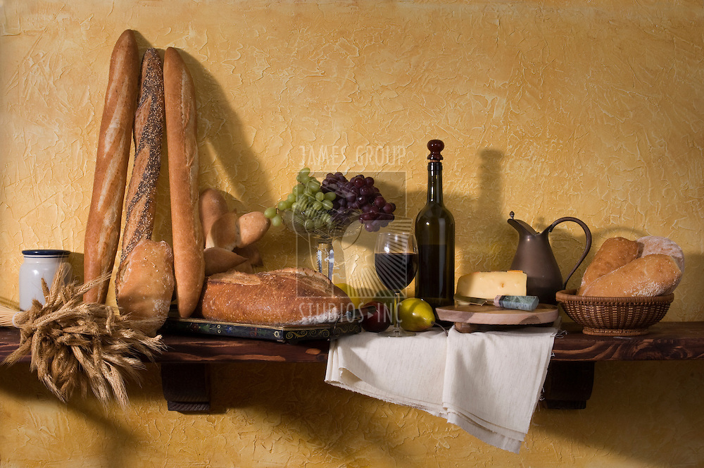Bread, cheese, wine and grapes against a tuscan plaster wall