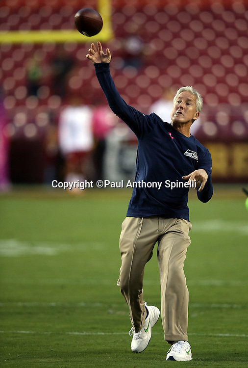 Seattle Seahawks head coach Pete Carroll throws a pass before the NFL week 5 regular season football game against the Washington Redskins on Monday, Oct. 6, 2014 in Landover, Md. The Seahawks won the game 27-17. ©Paul Anthony Spinelli